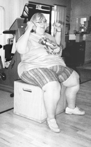 Photo of a woman lifting hand weights while sitting on a chair