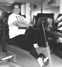Photo of a woman smiling while peddling an exercise bike